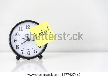 Procrastination delay and urgency concept with word later on yellow sticky paper over white alarm clock, bad time management. Сток-фото ©