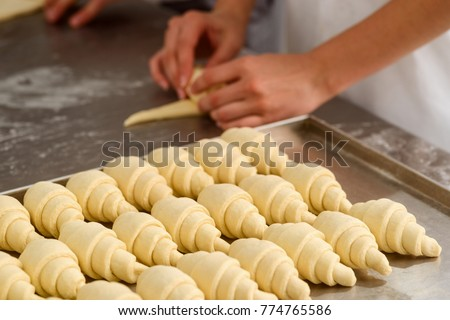 Producing classic croissants at the bakery shop. Woman is rolling dough into rolls for further baking. French pastry goods. #774765586