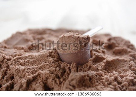 Product photograph of spoon or measuring scoop of whey protein. Whey protein powder sports bodybuilding supplement. Plastic scoop on wooden background with chocolate powder flavour.