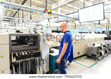 production and assembly of microelectronics in a hi-tech factory - man operates machine in production