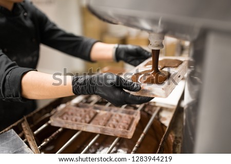 production, cooking and people concept - confectioner filling candy mold with chocolate at confectionery shop