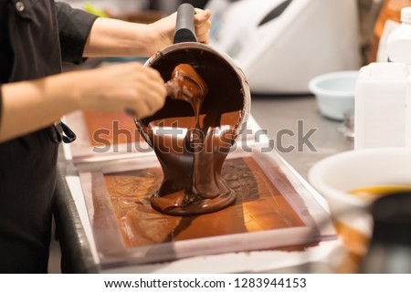 production, cooking and people concept - confectioner filling mold with chocolate at confectionery shop