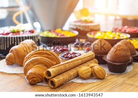 Production for the production of desserts. Croissants and cake in tartlets with cakes, nuts with condensed milk lie on a wooden table, torte