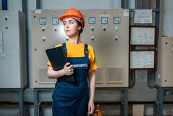 Production inspection. A young female worker in a uniform and a protective helmet, holding a folder. The concept of industrial manufactory.