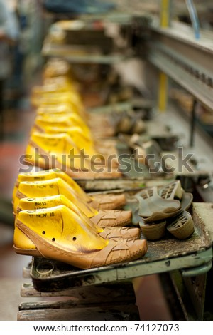 Production line in a footwear factory, half finished shoes on lasts