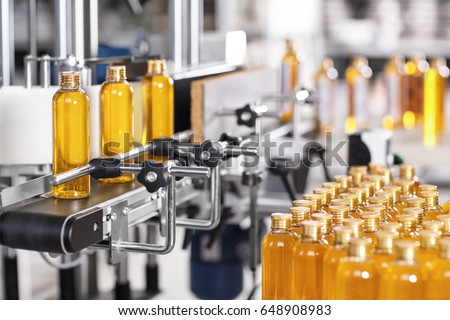 Production line of beauty and healthcare products at plant or factory. Process of manufacturing and packaging cosmetics goods. Glass or plastic bottles with screw caps standing on conveyor belt