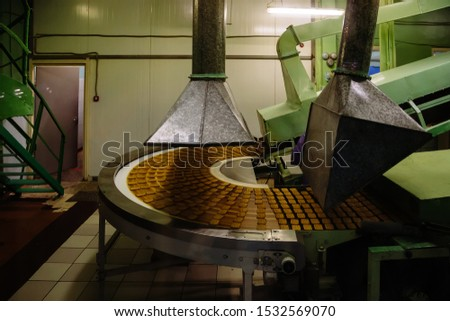 Production line of confectionery factory. Cookies moving on turning conveyor belt