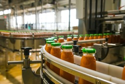Production line of juice on beverage plant or factory, modern computerized industrial equipment. Fresh juice in glass bottles