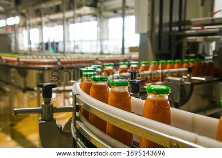 Production line of juice on beverage plant or factory, modern computerized industrial equipment. Fresh juice in glass bottles Foto stock ©