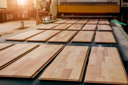 Production line of the wooden floor factory. CNC automatic woodworking machine. Industrial background