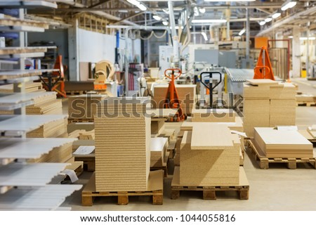 production, manufacture and woodworking industry concept - chipboards storing at furniture factory