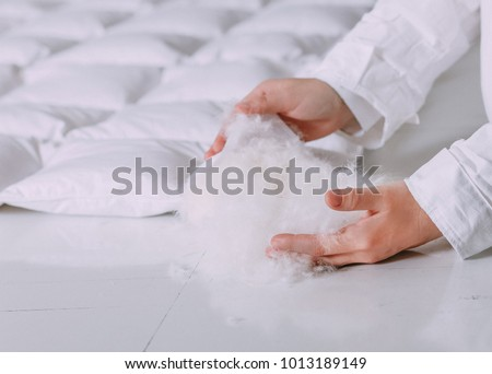 production of down duvets work with feather products light white fluff keeps in hands view from sides