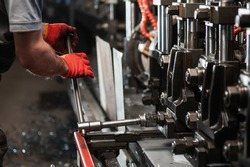 Production of metal products. Worker sets up a metal rolling mill
