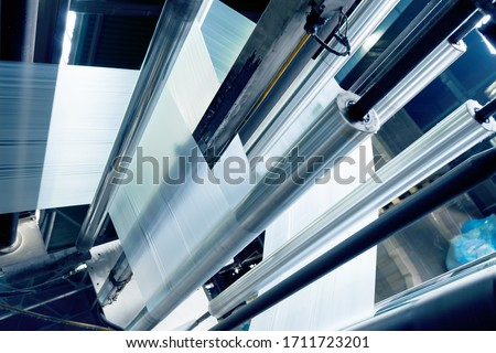 production of plastic packaging film on the automatic packing machine in food product factory. industrial and technology concept. Photo stock ©