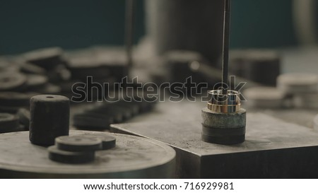 Production of rings. Jeweler working with wax model ring in his workshop. Craft jewelery making. Detail shot with low depth of field. Jeweler making handmade jewelry on vintage workbench. Craft of