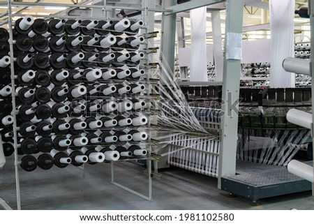 Production of white polypropylene flat yarn for the production of industrial bags. Allison-circular loom woven bag machine. Production of polypropylene sleeves. Shuttle Stockfoto ©