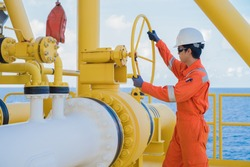 Production operator opening ball valve at offshore oil and gas wellhead remote platform to control gases and crude oil process, Petroleum industry occupational at offshore.