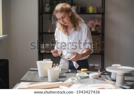 Production process of pottery. Application of glaze brush on ceramic ware. Сток-фото ©