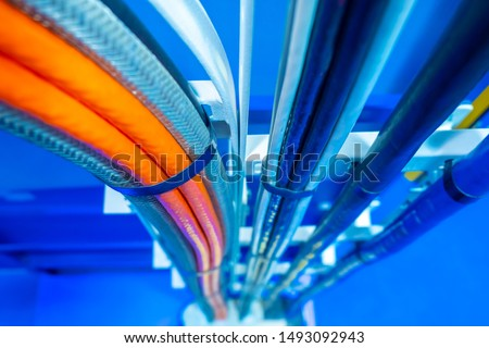 Production wiring. Electrical wiring in technical rooms. Electric wires are fastened by a plastic coupler. Cable wiring. Network engineering. Orange and deep blue electric wires.Work as an electrician #1493092943