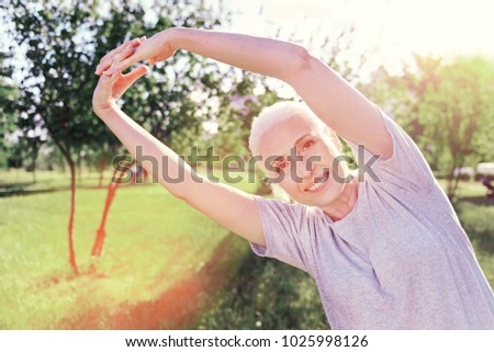 Productive morning. Close up of positive elderly woman keeping hands up while bending to left and smiling #1025998126
