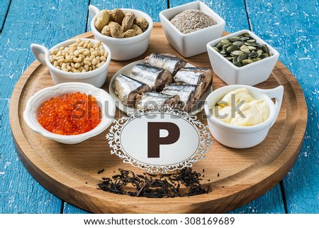 Products containing phosphorus (black tea, red caviar, pine nuts, peanuts, bran, sardines, pumpkin seeds, processed cheese) on a round cutting board and a blue wooden background