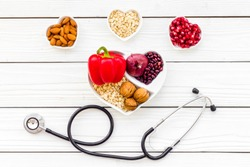 Products good for heart and blood vessels. Vegetables, fruits, nuts in heart shaped bowl near stethoscope on white wooden background top view