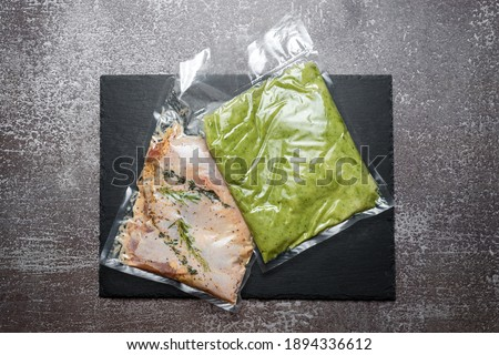 Products in vacuum packaging on black slate board. Chicken meat with herbs and green beans puree, vacuum sealed food ready for sous vide cooking. Sous-vide, new technology cuisine in quarantine time. Photo stock ©