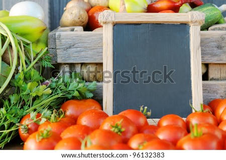 Products on the market. Tomatoes and a price tag in a wooden frame. Price list for food.