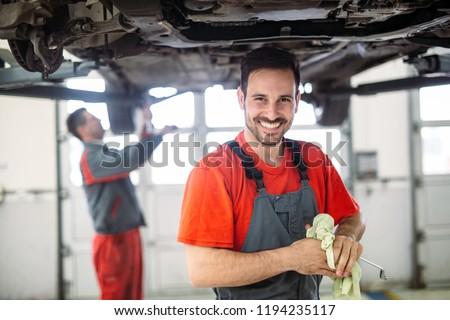Profecional car mechanic changing motor oil at maintenance repair service station #1194235117