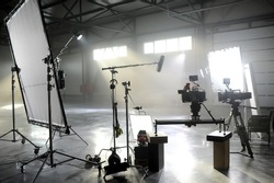 Profesional video studio.Behind-the-scenes of a video shooting.Behind the shooting production silhouette of camera and equipment in studio.Selective focus.