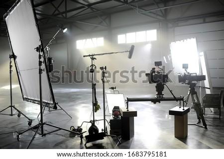 Photo of  Profesional video studio.Behind-the-scenes of a video shooting.Behind the shooting production silhouette of camera and equipment in studio.Selective focus.