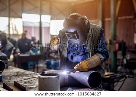Profesional welder in protective uniform and mask welding metal pipe on the industrial table with other workers behind in the industrial workshop. #1015084627