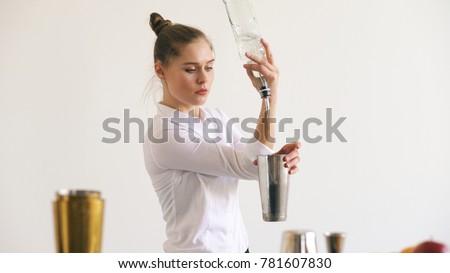 Professinal bartender girl juggling bottles and shaking cocktail at mobile bar table on white background #781607830