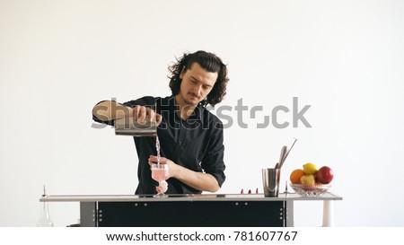 Professinal bartender man shaking cocktail at mobile bar table on white background #781607767