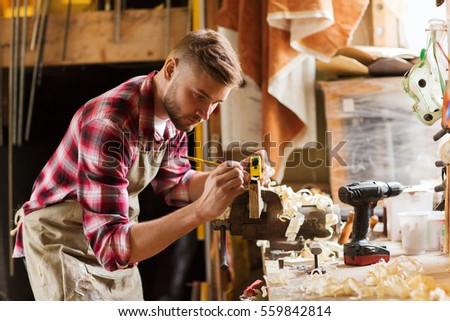 profession, carpentry, woodwork and people concept - carpenter with ruler measuring wood plank at workshop