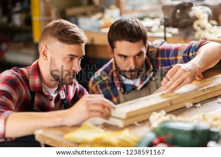 profession, carpentry, woodwork and people concept - two carpenters measuring wooden board at workshop