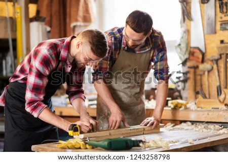 profession, carpentry, woodwork and people concept - two carpenters with ruler measuring wooden board at workshop
