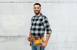 profession, construction and building concept - happy smiling male worker or builder in goggles with tool belt over grey concrete background