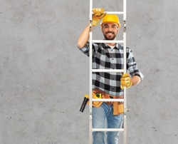 profession, construction and building concept - happy smiling male worker or builder in helmet and gloves climbing up ladder over grey concrete background