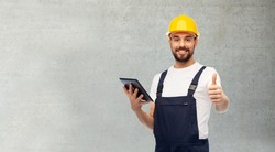 profession, construction and building concept - happy smiling male worker or builder in yellow helmet and overall with tablet pc computer showing thumbs up over grey concrete background