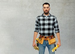profession, construction and building concept - male worker or builder with level and tool belt over grey concrete background