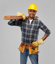 profession, construction and building - happy smiling indian carpenter or builder in helmet with tool belt and wooden boards over grey background
