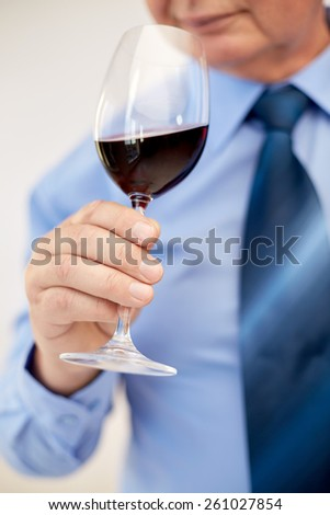 profession, drinks, holidays and people concept - close up of senior man drinking red wine from glass
