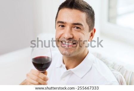 profession, drinks, leisure, holidays and people concept - happy man drinking red wine from glass at home