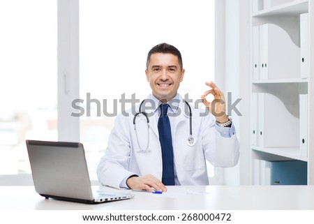 profession, gesture, people, technology and medicine concept - smiling male doctor in white coat with laptop pomputer showing ok in medical office