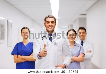 profession, people, health care, gesture and medicine concept - group of happy medics or doctors at hospital corridor showing thumbs up