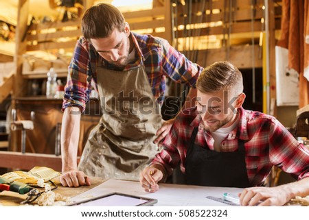 profession, technology and people concept - two workmen with tablet pc computer and blueprint at workshop - Shutterstock ID 508522324