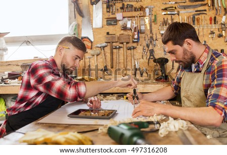 profession, technology and people concept - two workmen with tablet pc computer, dividers or compass and blueprint at workshop - Shutterstock ID 497316208
