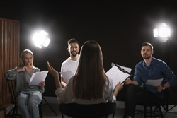 Professional actors reading their scripts during rehearsal in theatre