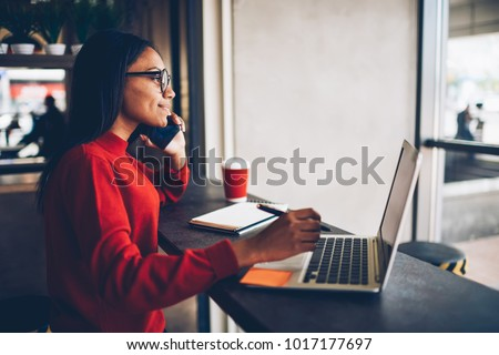 Professional African american copywriter talking about new project on mobile earning money online.Attractive dark skinned manager in stylish spectacles checking banking account talking with operator